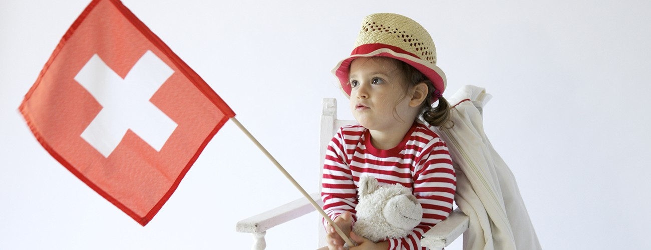 Child holding a Swiss flag